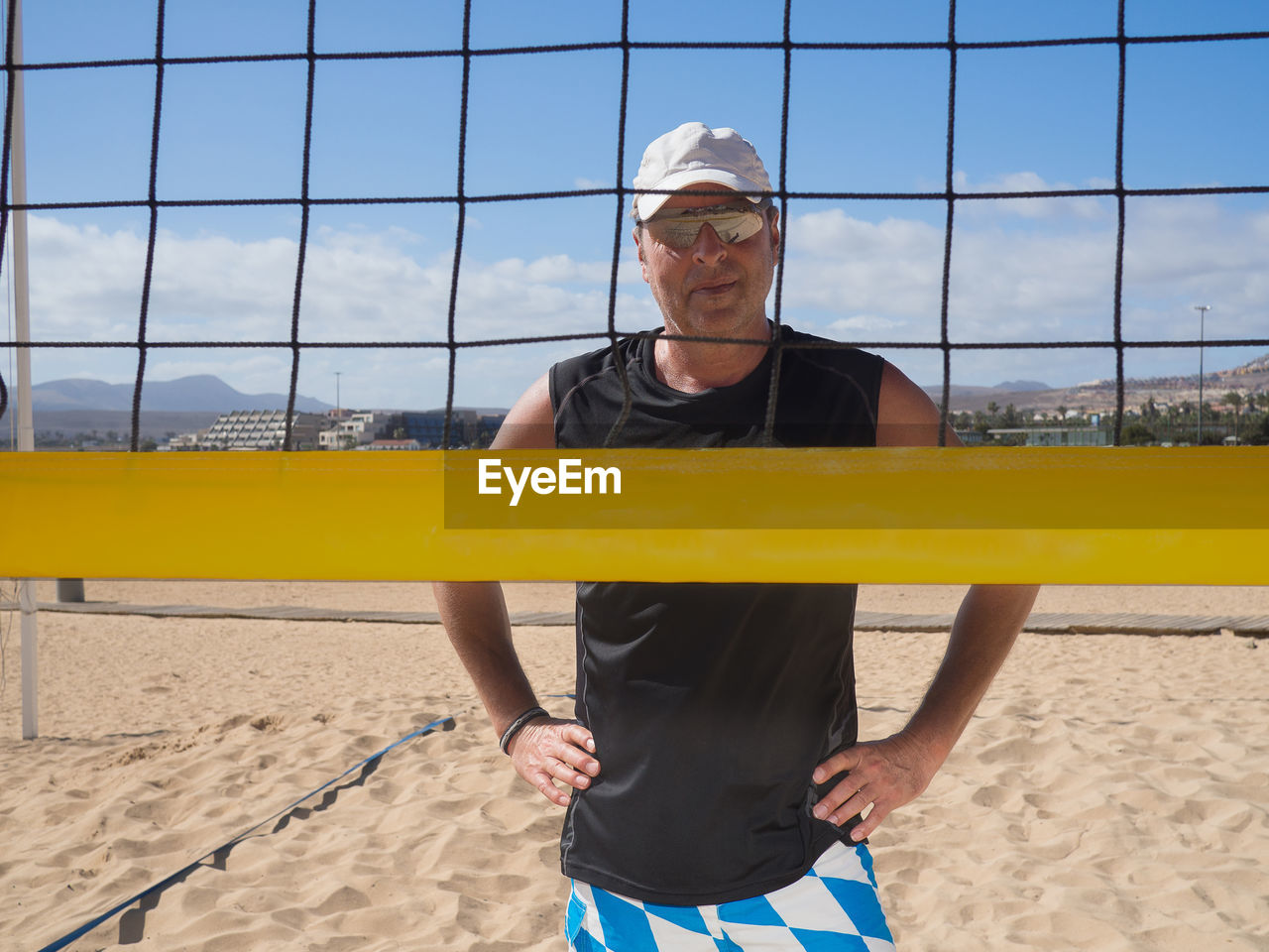 Portrait of man in sunglasses standing by volleyball net against sky