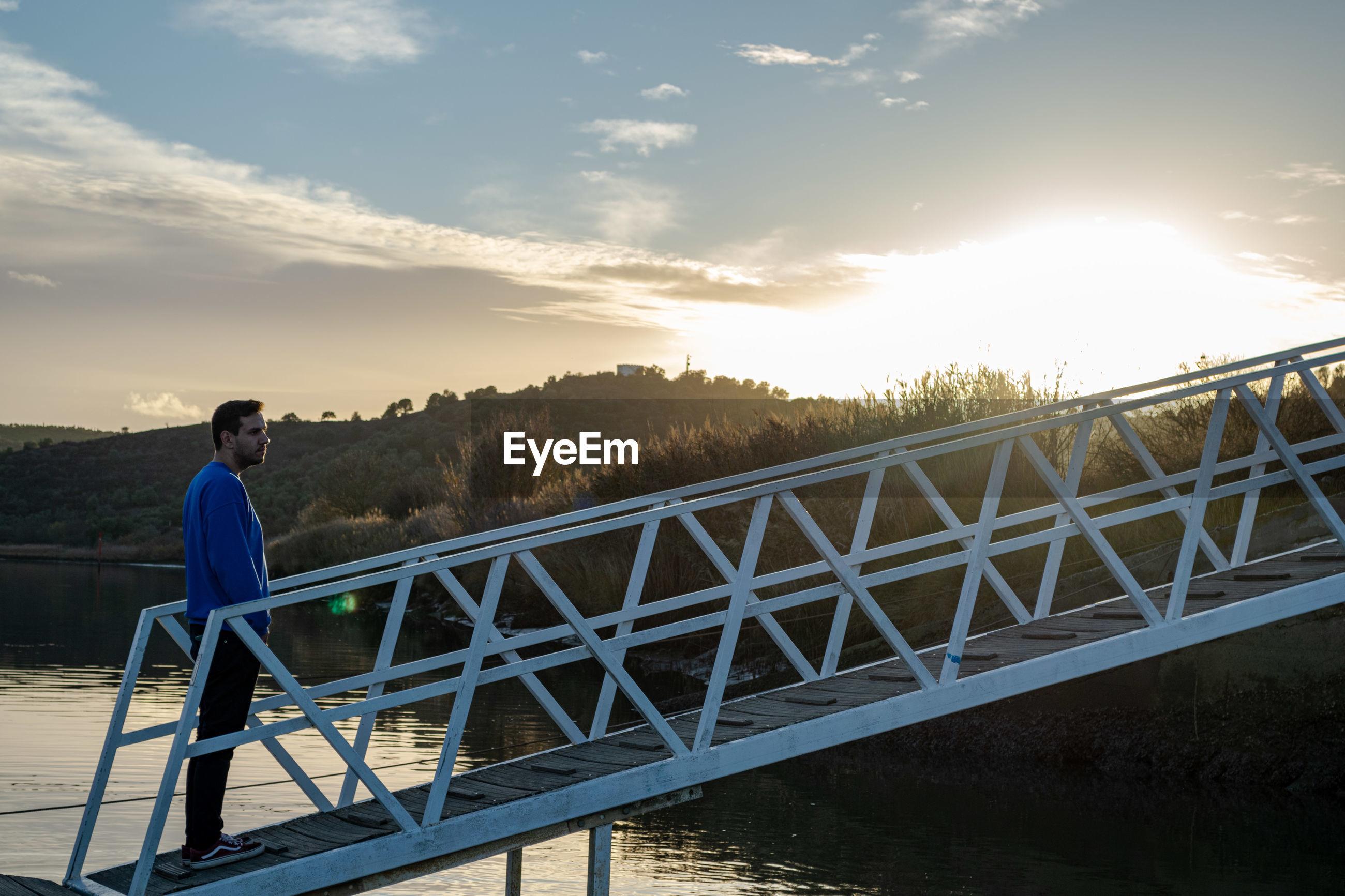 Man standing on bridge against sky during sunset