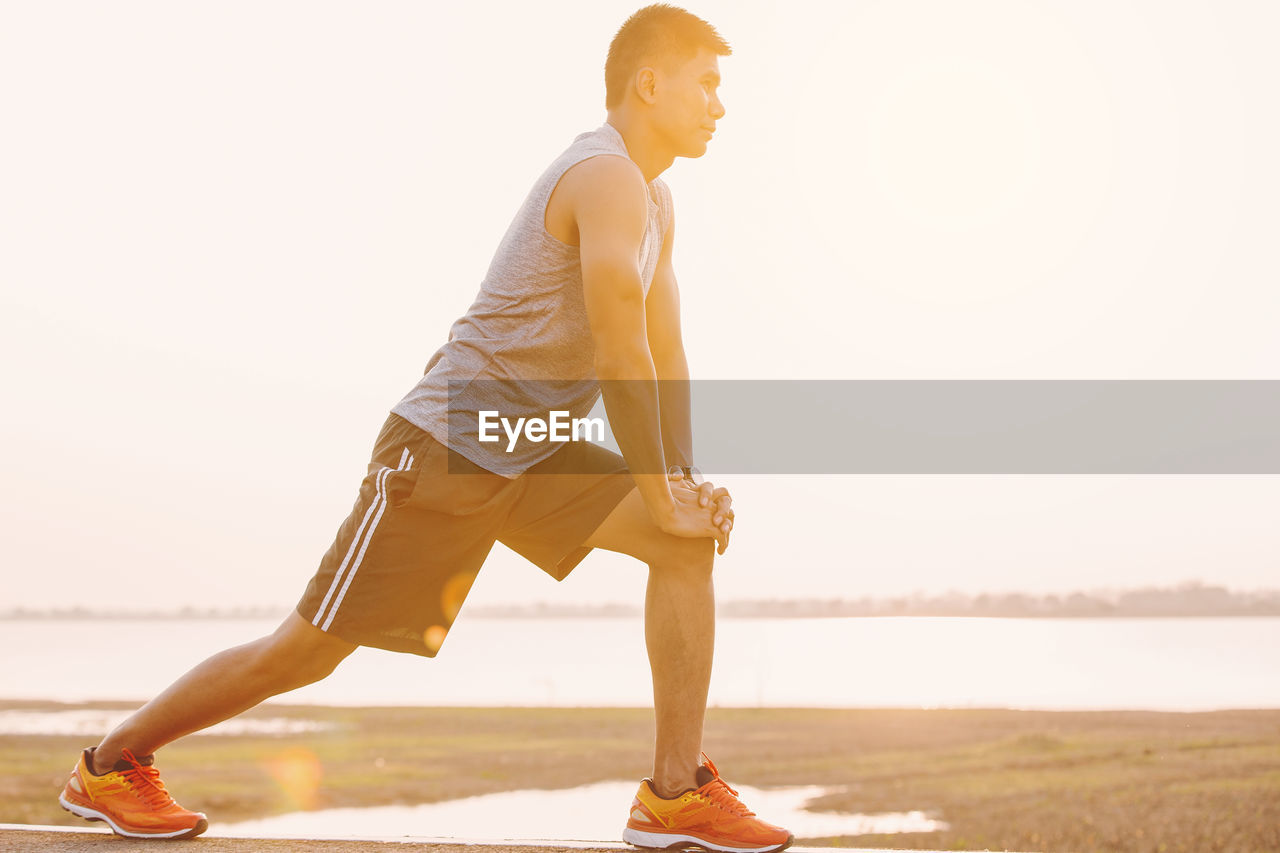 lifestyles, full length, real people, one person, water, sky, young adult, leisure activity, side view, nature, young men, men, clear sky, casual clothing, beach, sunlight, land, effort