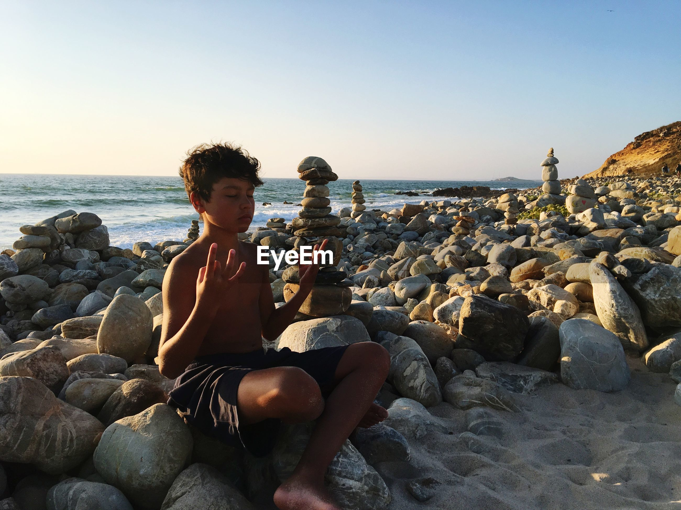 Shirtless boy with eyes closed meditating while sitting on rocks at beach against clear sky during sunset