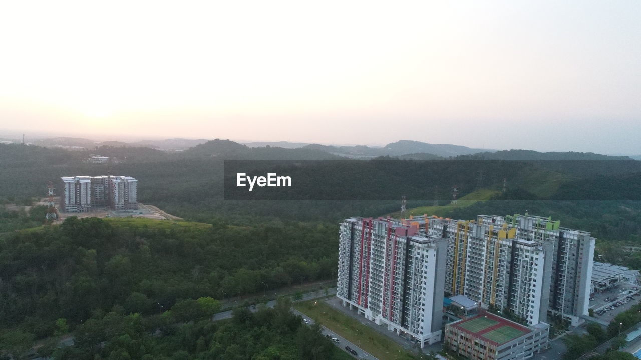 mountain, architecture, built structure, building exterior, high angle view, cityscape, no people, sunset, outdoors, scenics, nature, city, beauty in nature, tree, skyscraper, sky, clear sky, day