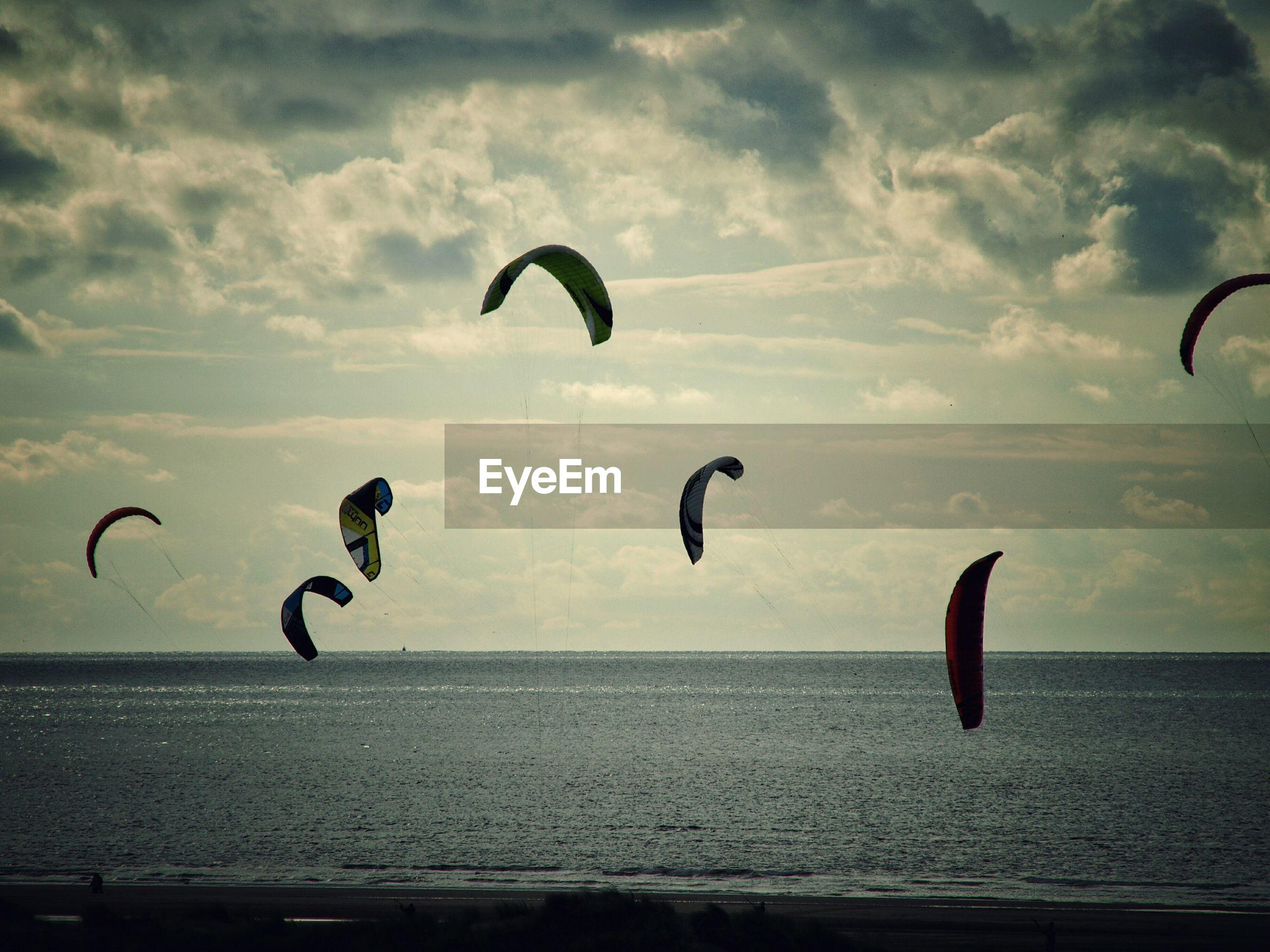 BIRDS FLYING OVER SEA AGAINST CLOUDY SKY