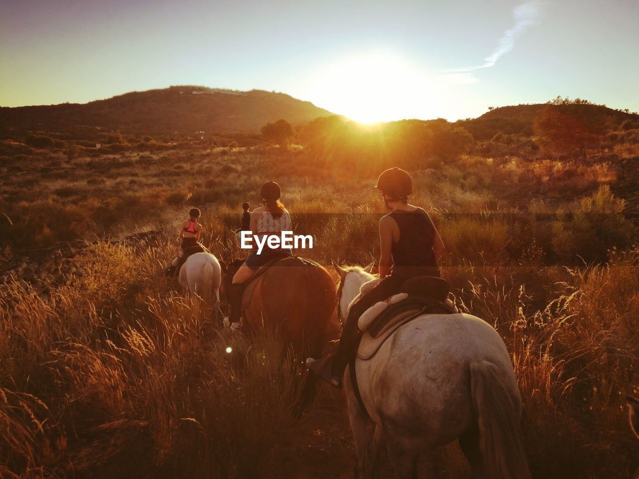 Rear View Of Mother With Children Horseback Riding On Field During Sunset