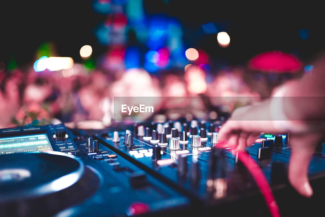 audio equipment, music, arts culture and entertainment, sound mixer, sound recording equipment, real people, night, dj, nightlife, human hand, club dj, equipment, control, nightclub, technology, hand, occupation, human body part, record, selective focus, skill, mixing, finger, electrical equipment