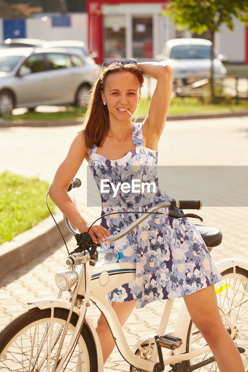 WOMAN RIDING BICYCLE ON CITY