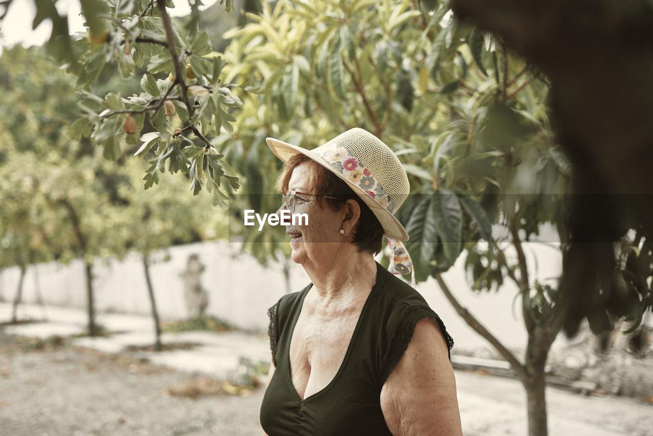 WOMAN WEARING HAT LOOKING AWAY OUTDOORS