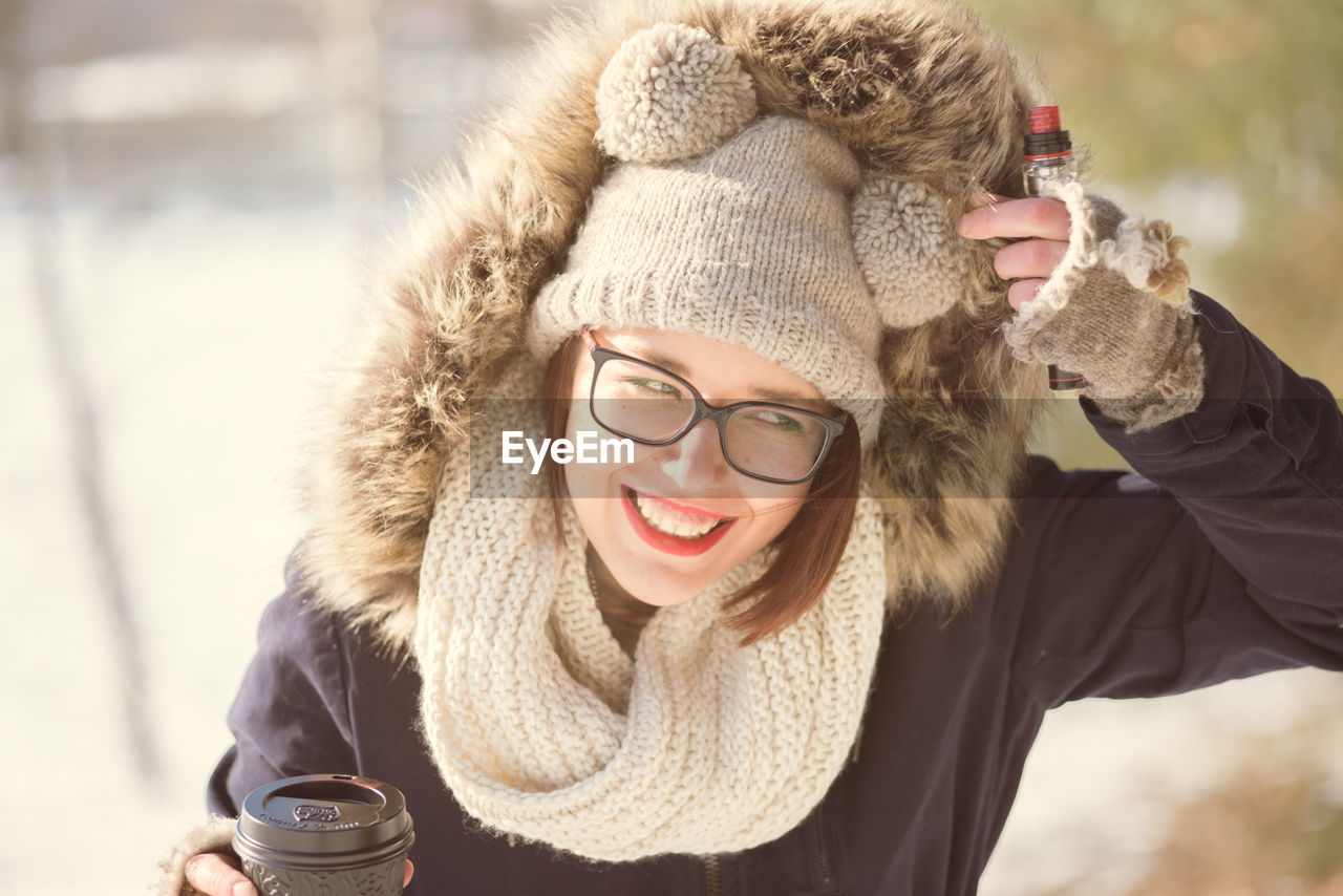 warm clothing, winter, smiling, happiness, young adult, real people, cold temperature, young women, one person, front view, coffee cup, knit hat, outdoors, focus on foreground, scarf, toothy smile, leisure activity, day, eyeglasses, lifestyles, portrait, coffee - drink, drinking, headshot, cheerful, looking at camera, holding, snow, beautiful woman, drink, close-up, nature, adult, people