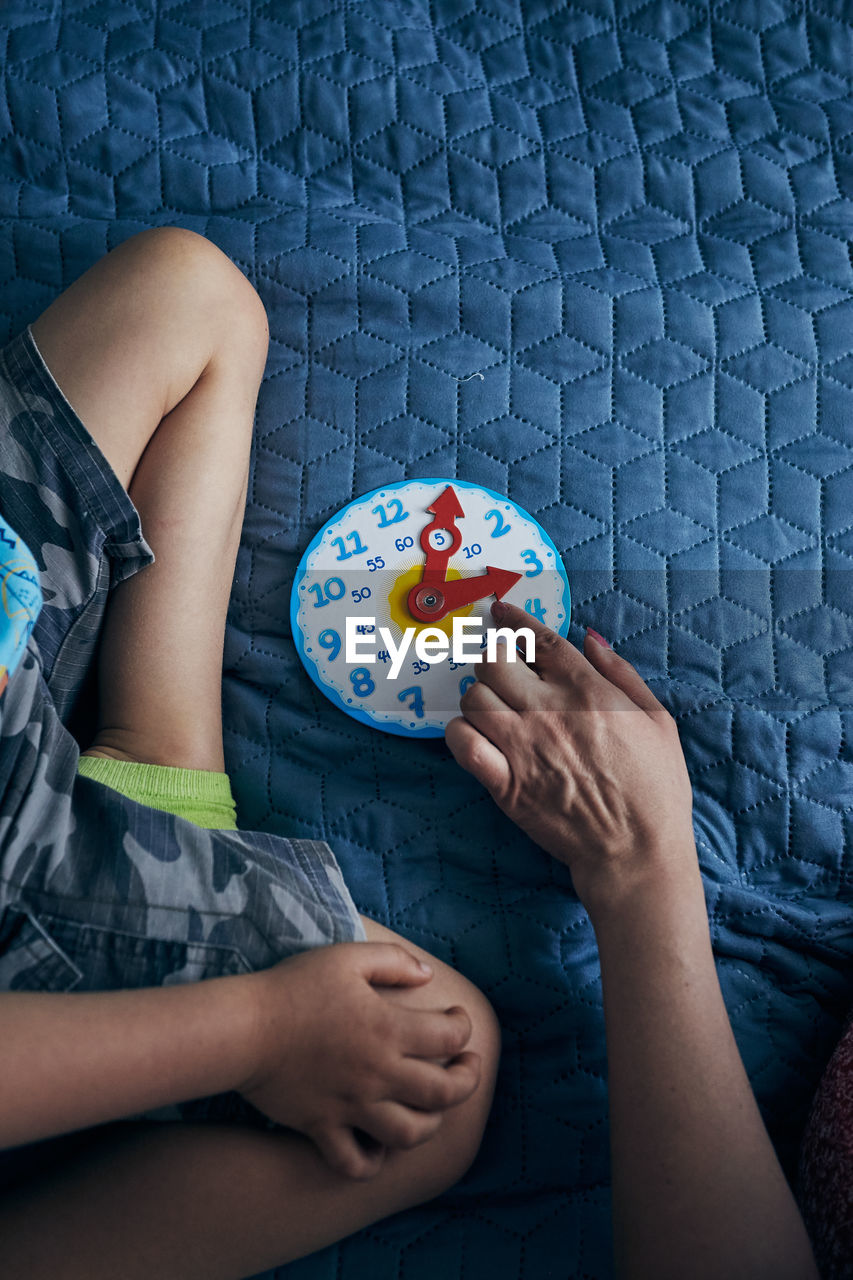Cropped hand of woman pointing at toy clock by boy on bed