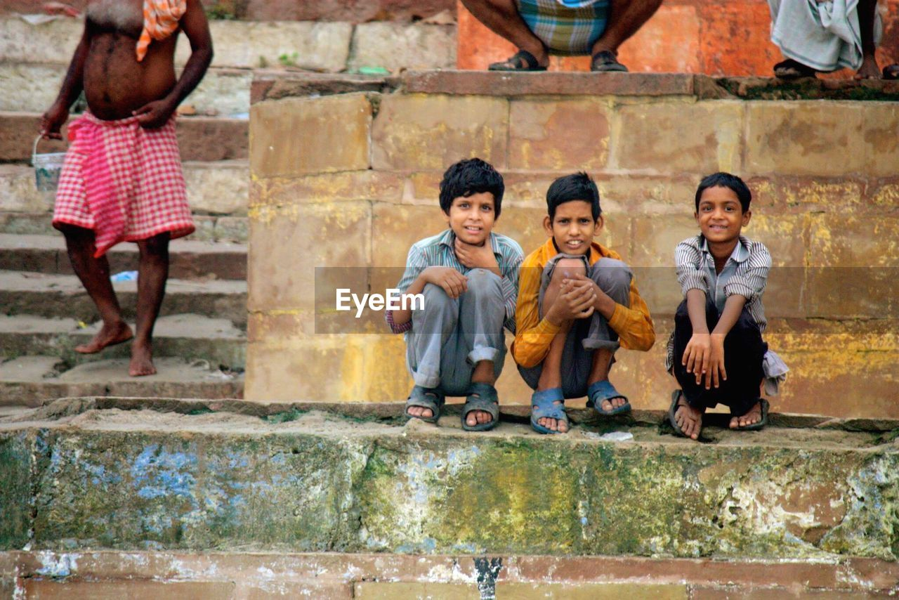 full length, childhood, boys, outdoors, looking at camera, day, steps, sitting, portrait, real people, building exterior, architecture, standing, friendship, child, togetherness, playing, people, adult