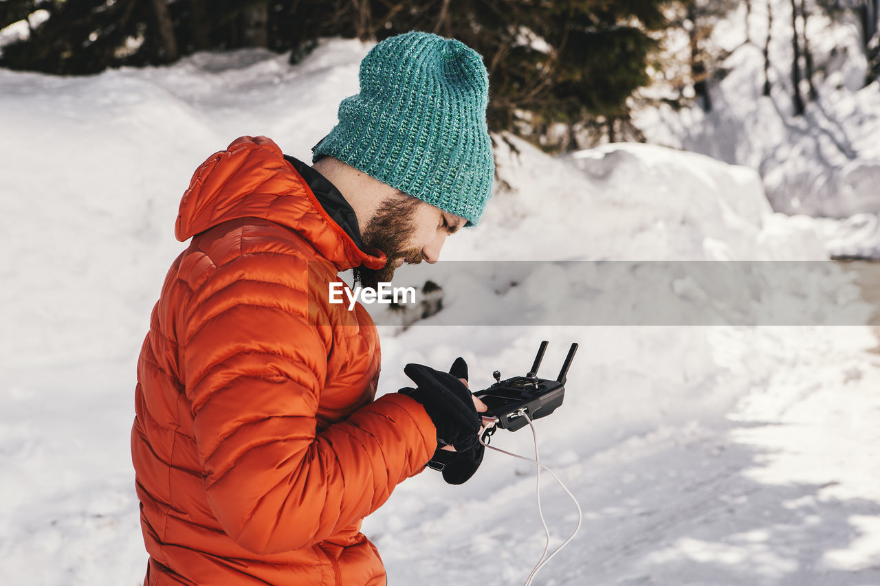 Side View Of Man Using Remote Control While Standing On Snow Covered Field