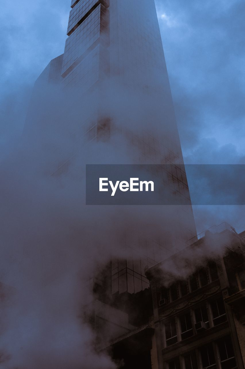 Low angle view of smoke coming out from buildings against sky