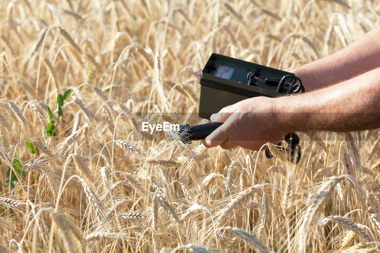 PERSON HOLDING CAMERA WHILE STANDING IN FIELD