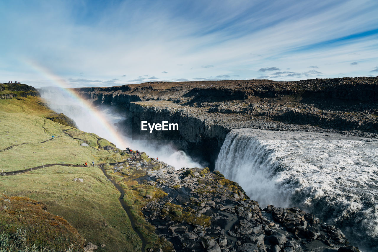 Scenic View Of Rainbow Over Waterfall In Crater