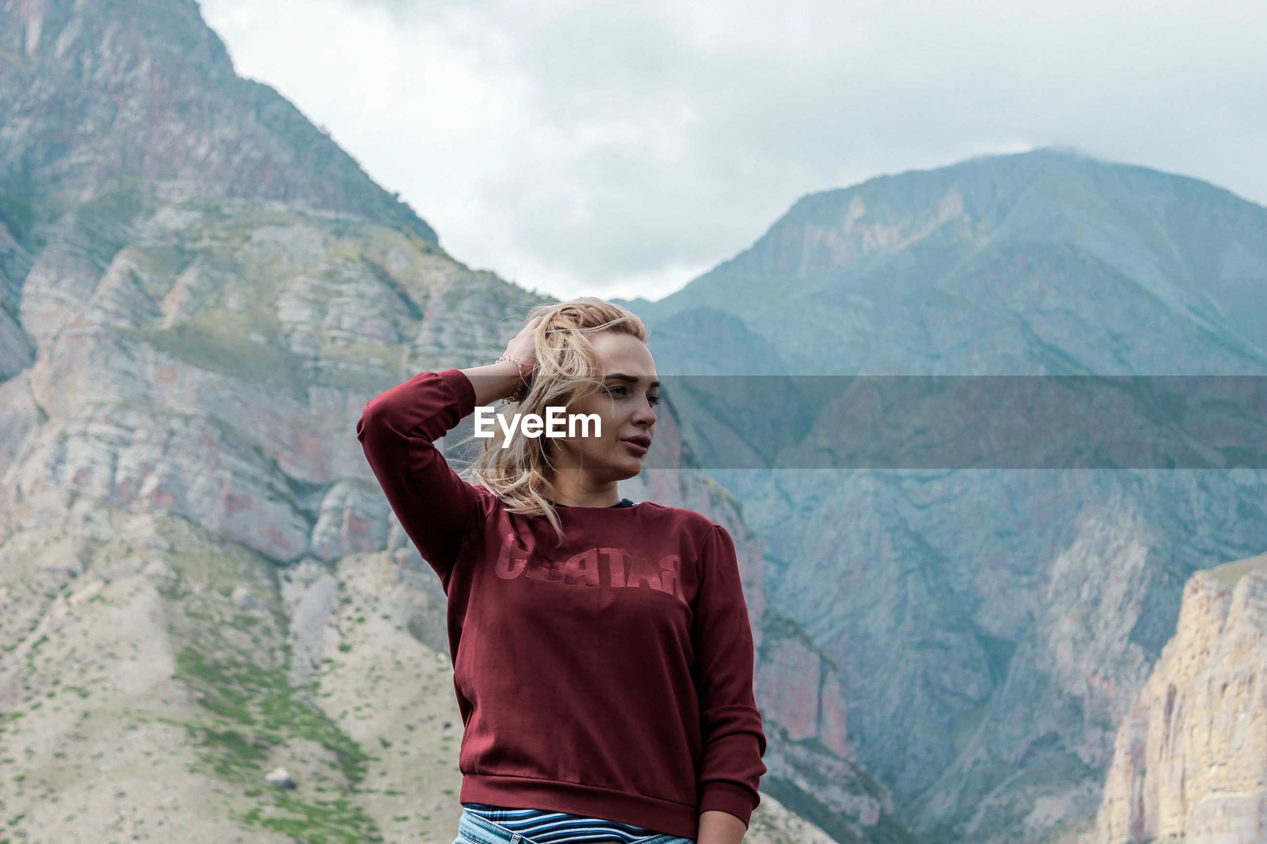Young woman looking away while standing against mountain range