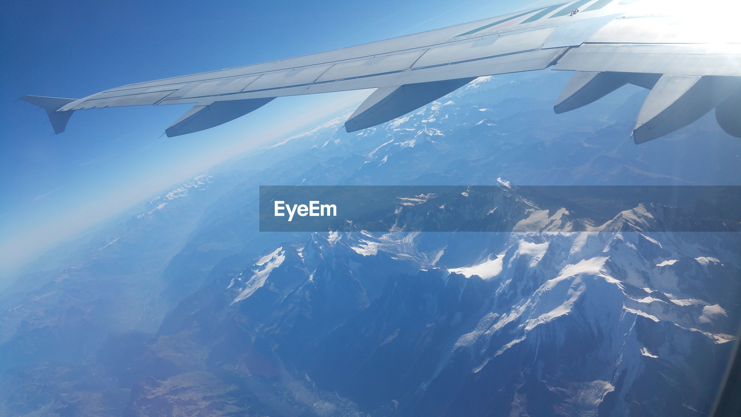 Cropped image of airplane flying above mountains