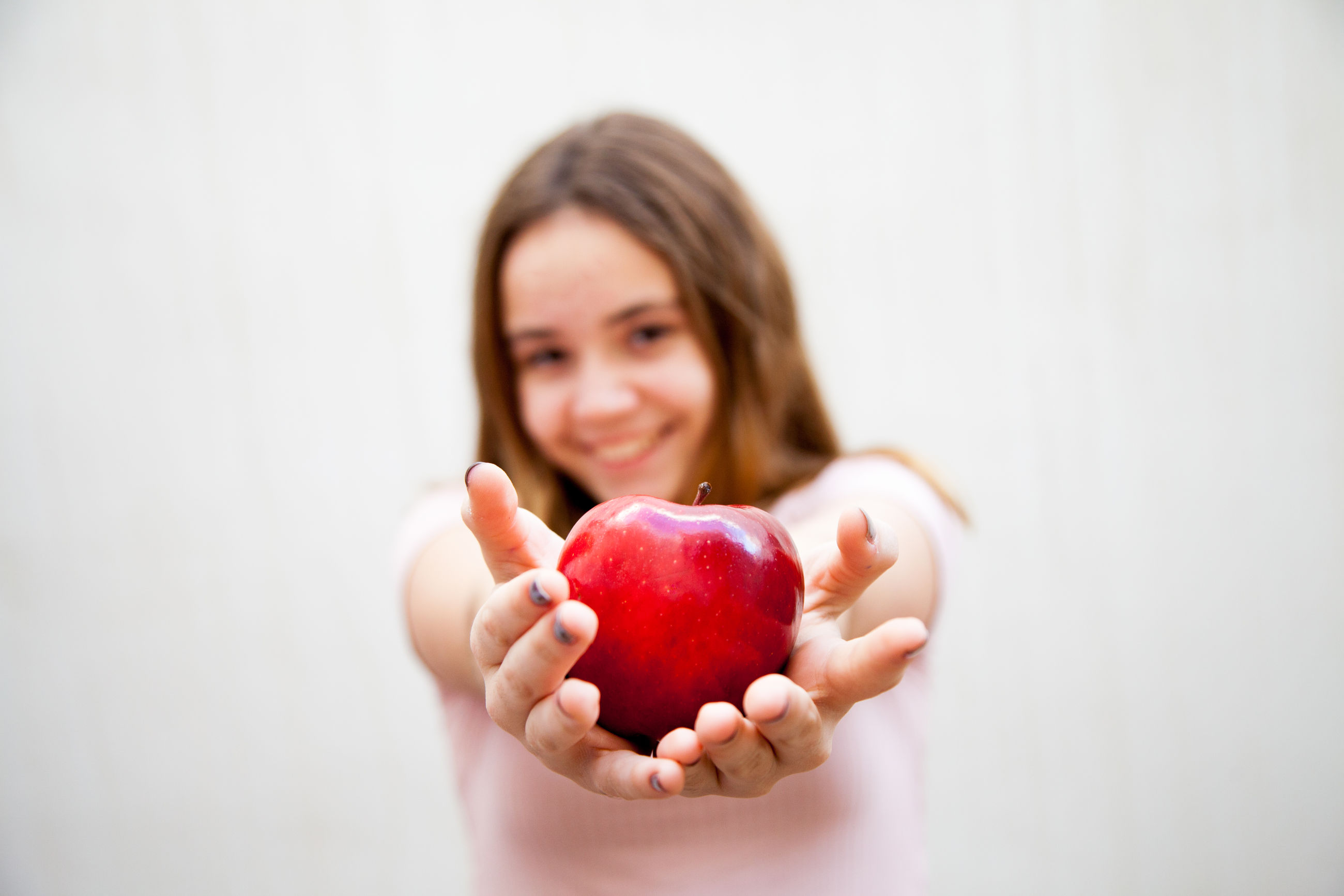 Portrait of girl holding apple while standing against white wall