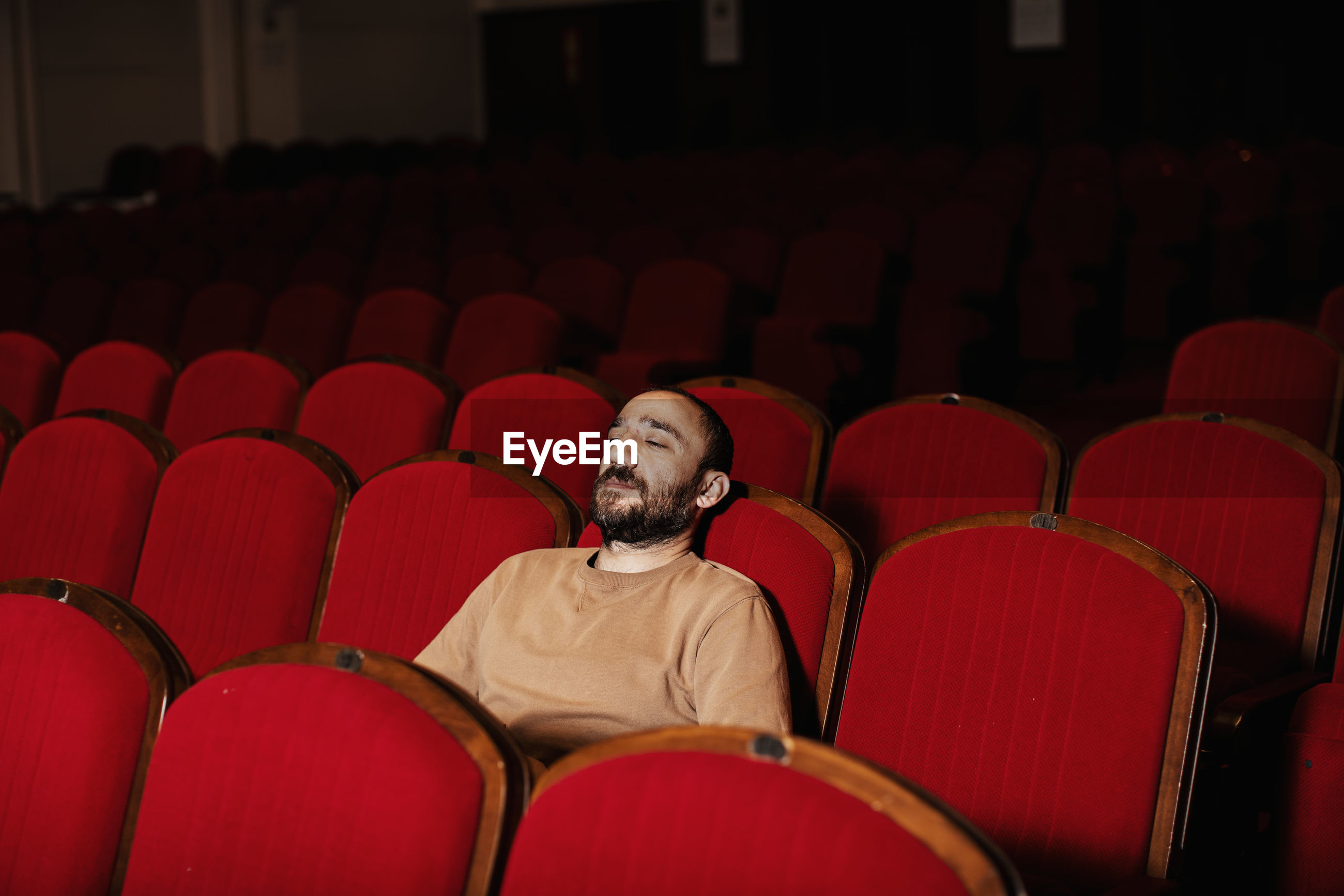 Man looking away while sitting on chair in theater