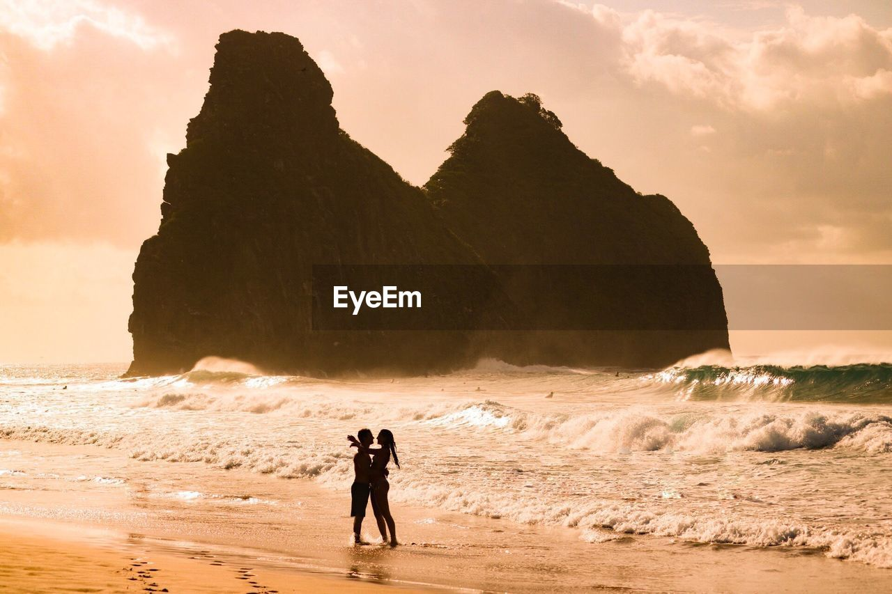 Couple Embracing While Standing At Beach Against Rock Formations During Sunset