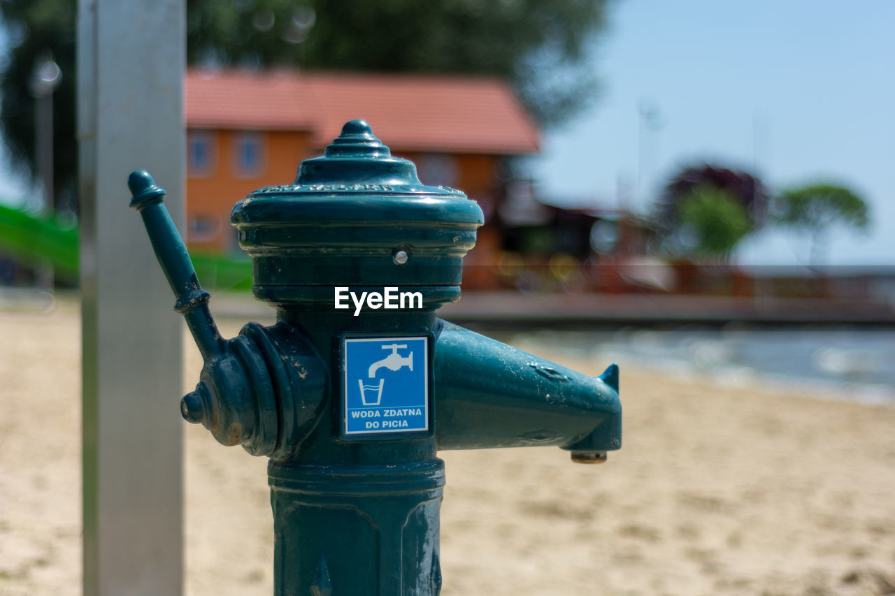 CLOSE-UP OF FIRE HYDRANT AGAINST BLUE WALL