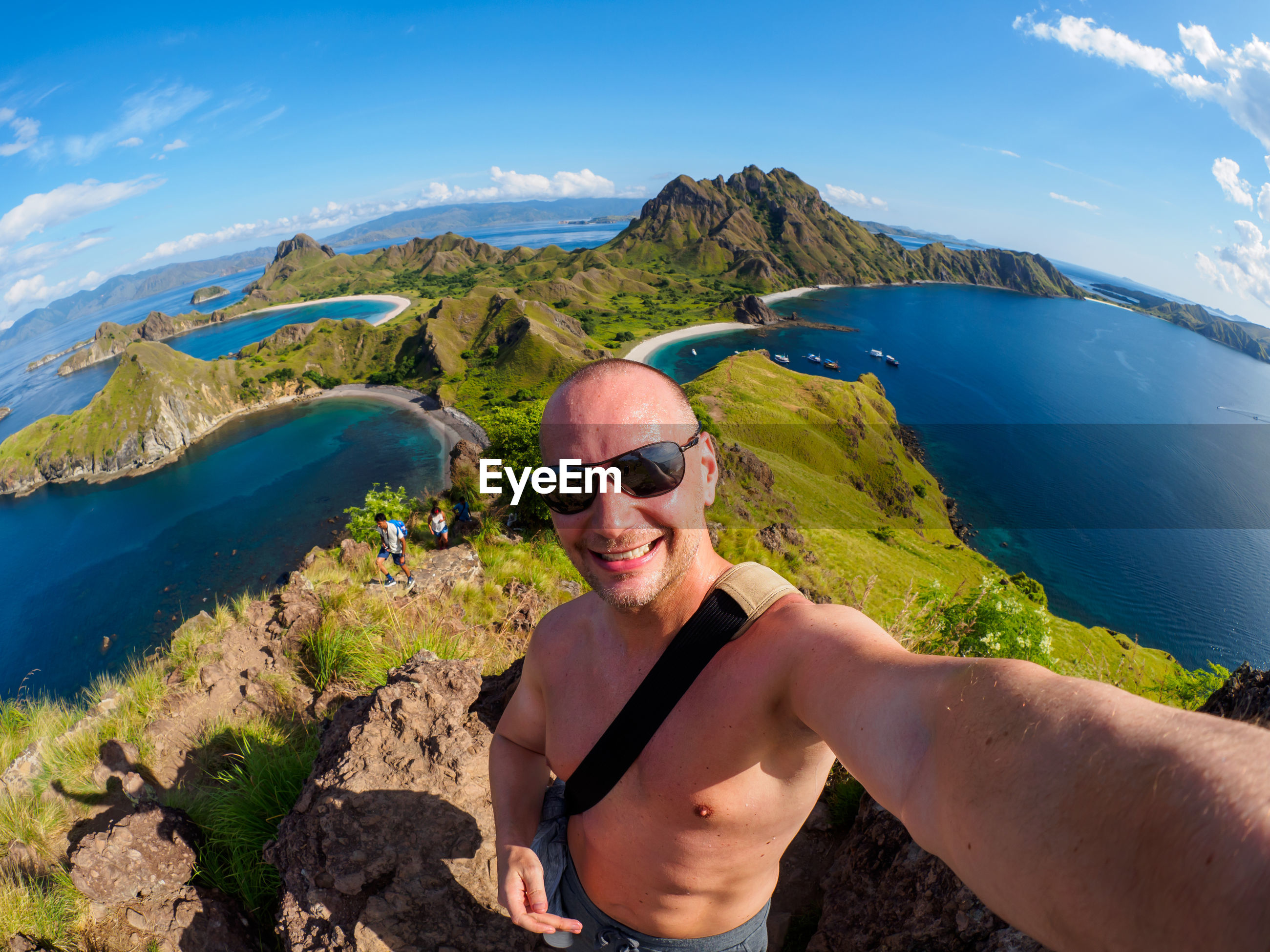 Fish-eye lens portrait of shirtless man standing on cliff by sea