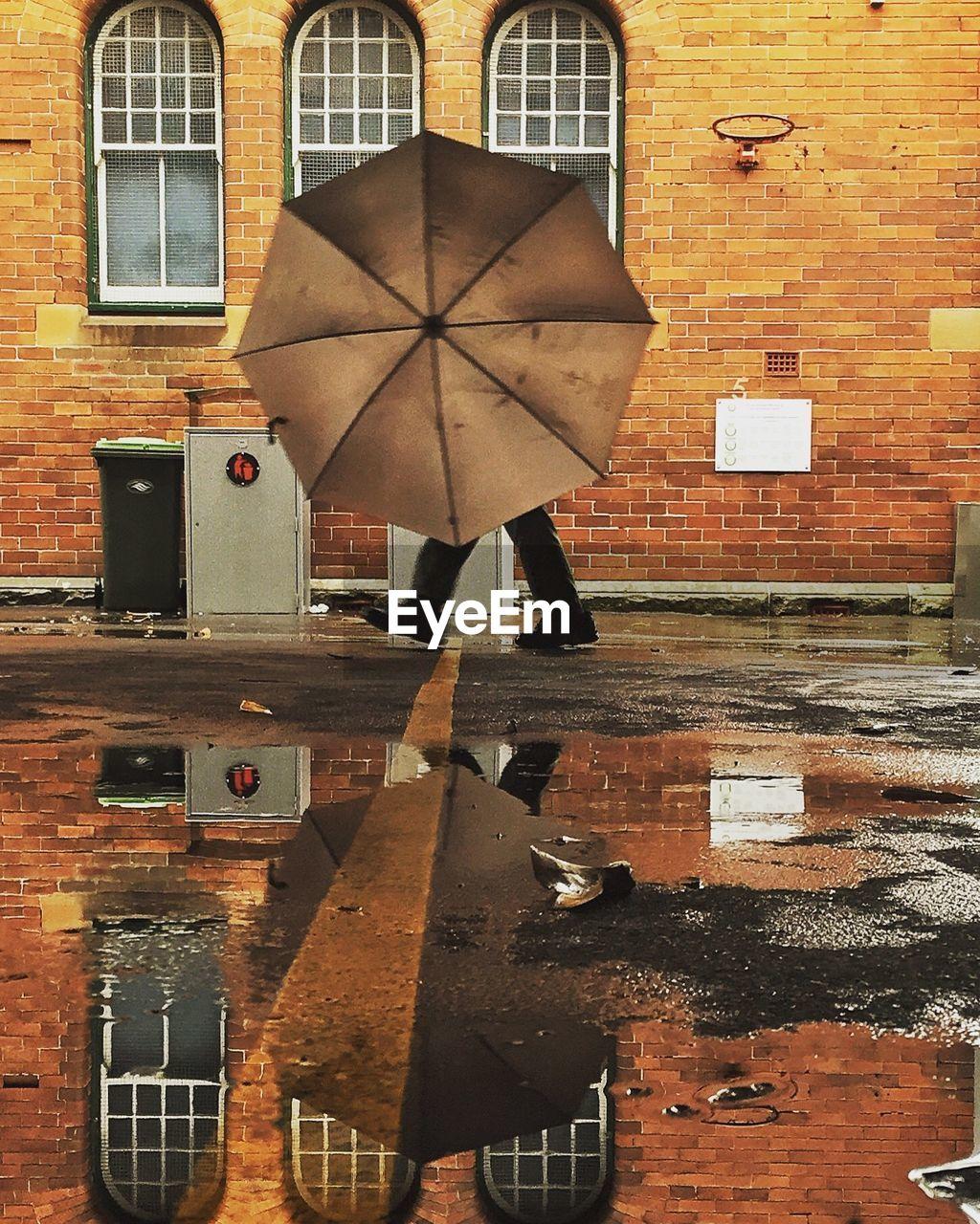 Man With Umbrella Walking On Wet Road During Rainy Season