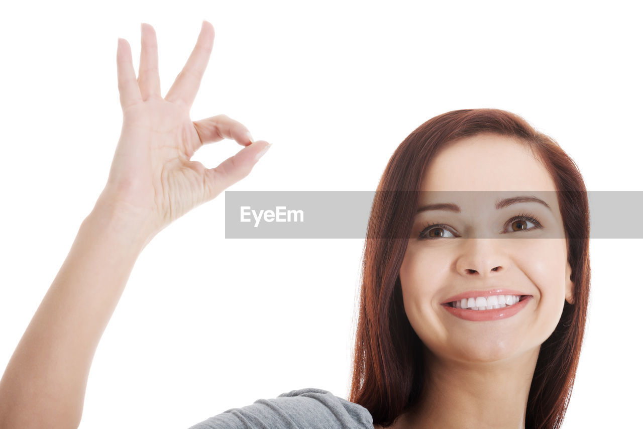 Mid Adult Woman Showing Ok Sign Against White Background