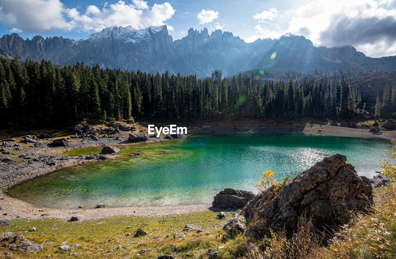 Lake carezza  lake with deep blue colored water and the dolomite mountain range in italy, europe.