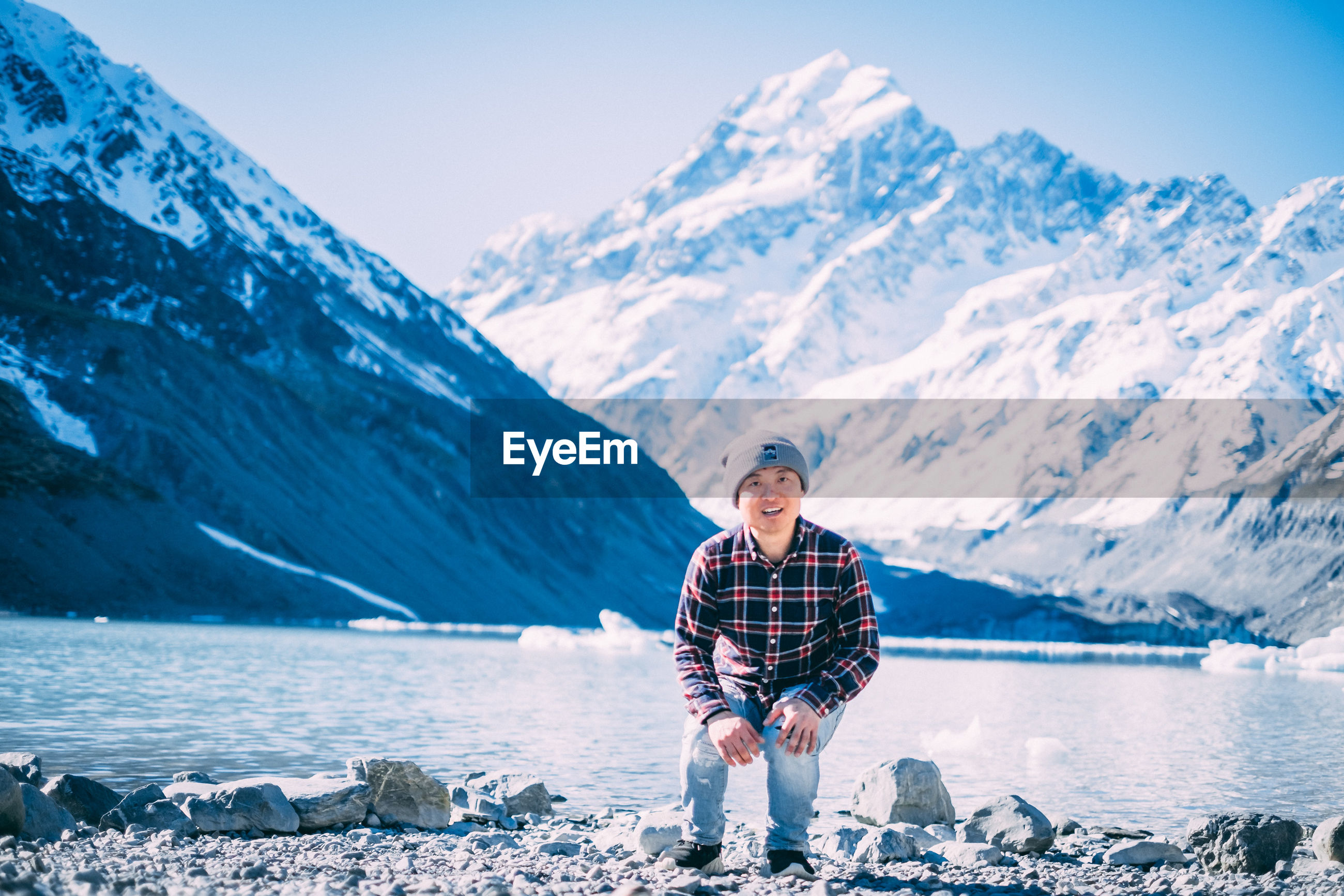 FULL LENGTH OF MAN STANDING BY LAKE AGAINST MOUNTAINS