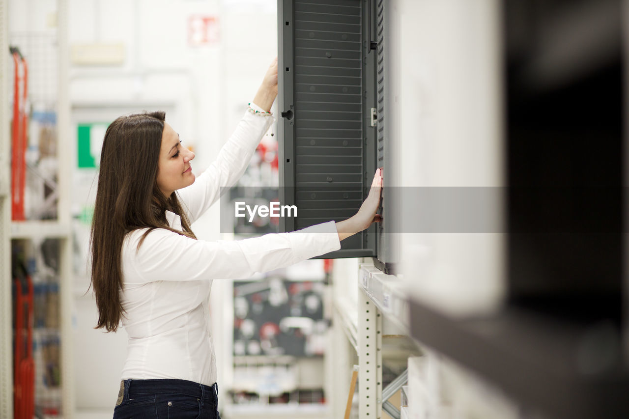 Side View Of Smiling Woman Looking At Cabinet In Store