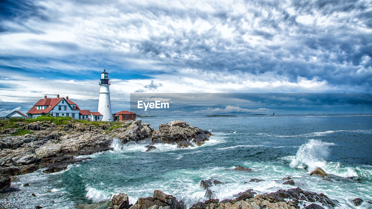 Scenic view of portland head light lighthouse by sea against sky