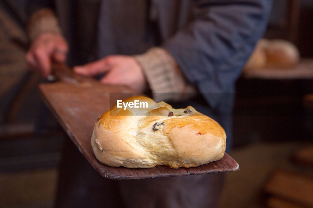Close-up of bread on serving board being held by man