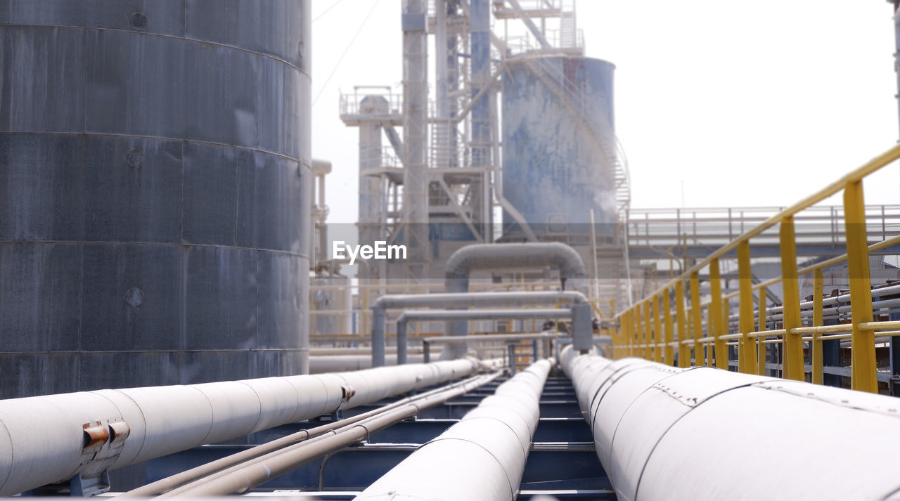 industry, factory, pipeline, pipe - tube, fuel and power generation, technology, storage tank, built structure, architecture, building exterior, day, oil industry, refinery, metal, outdoors, oil refinery, connection, nature, no people, low angle view, industrial equipment, fuel storage tank, chemical plant, pollution, silver colored