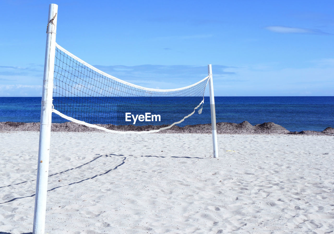 beach, sea, land, net - sports equipment, sky, water, sand, beauty in nature, horizon, beach volleyball, horizon over water, tranquility, nature, scenics - nature, day, tranquil scene, no people, sport, blue, outdoors