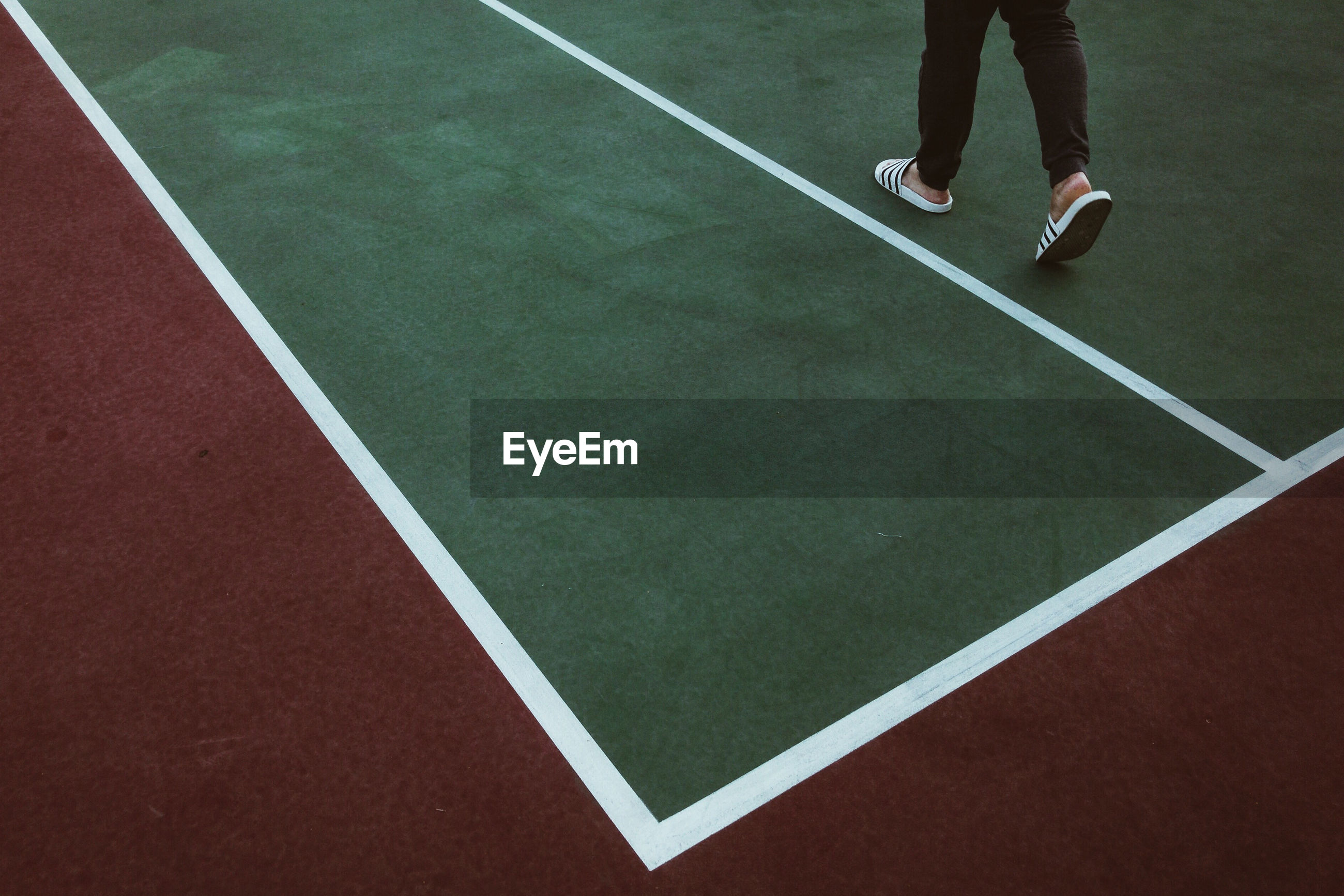 Low section of person standing on tennis court.