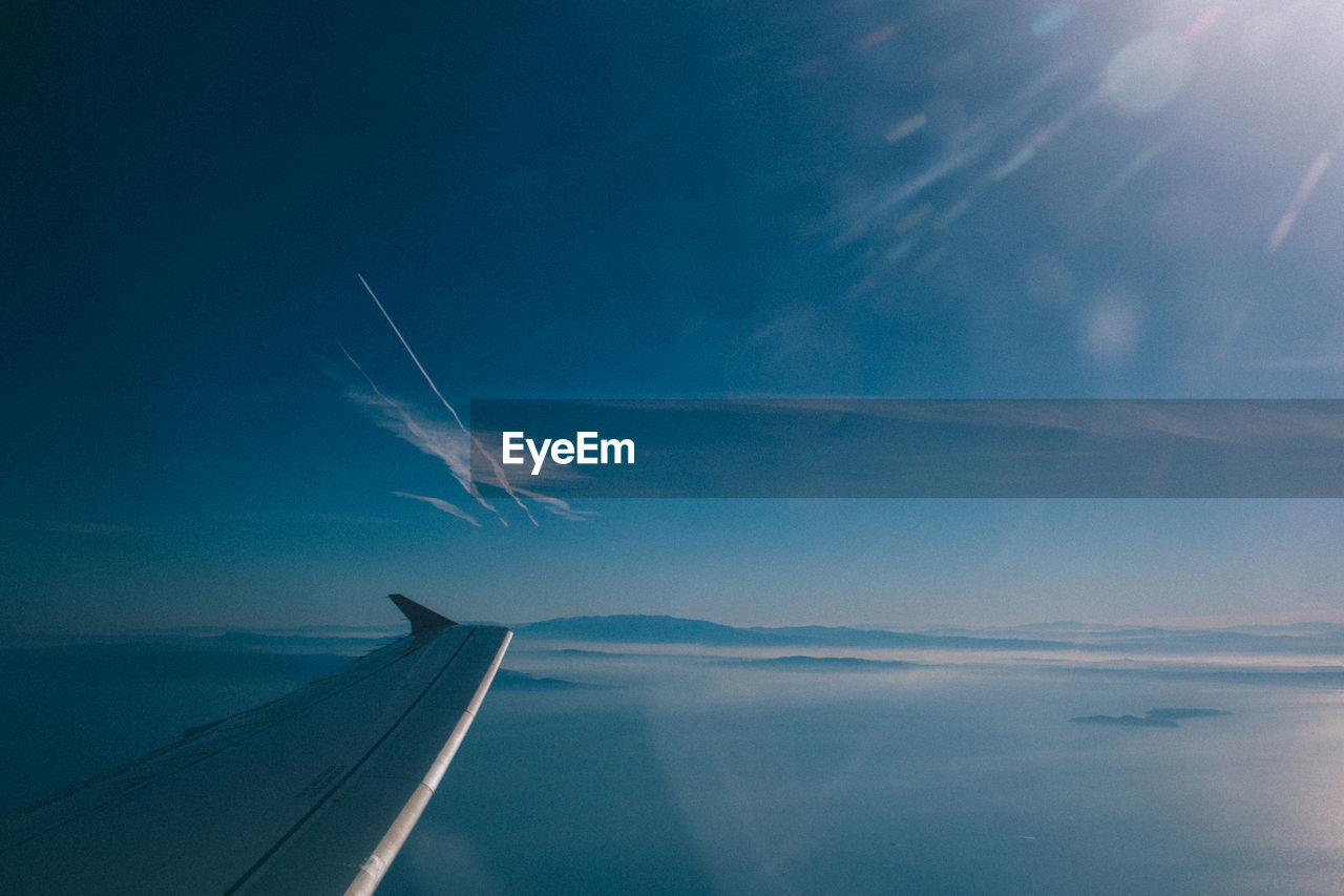 Cropped image of aircraft wing over sea against sky seen from window