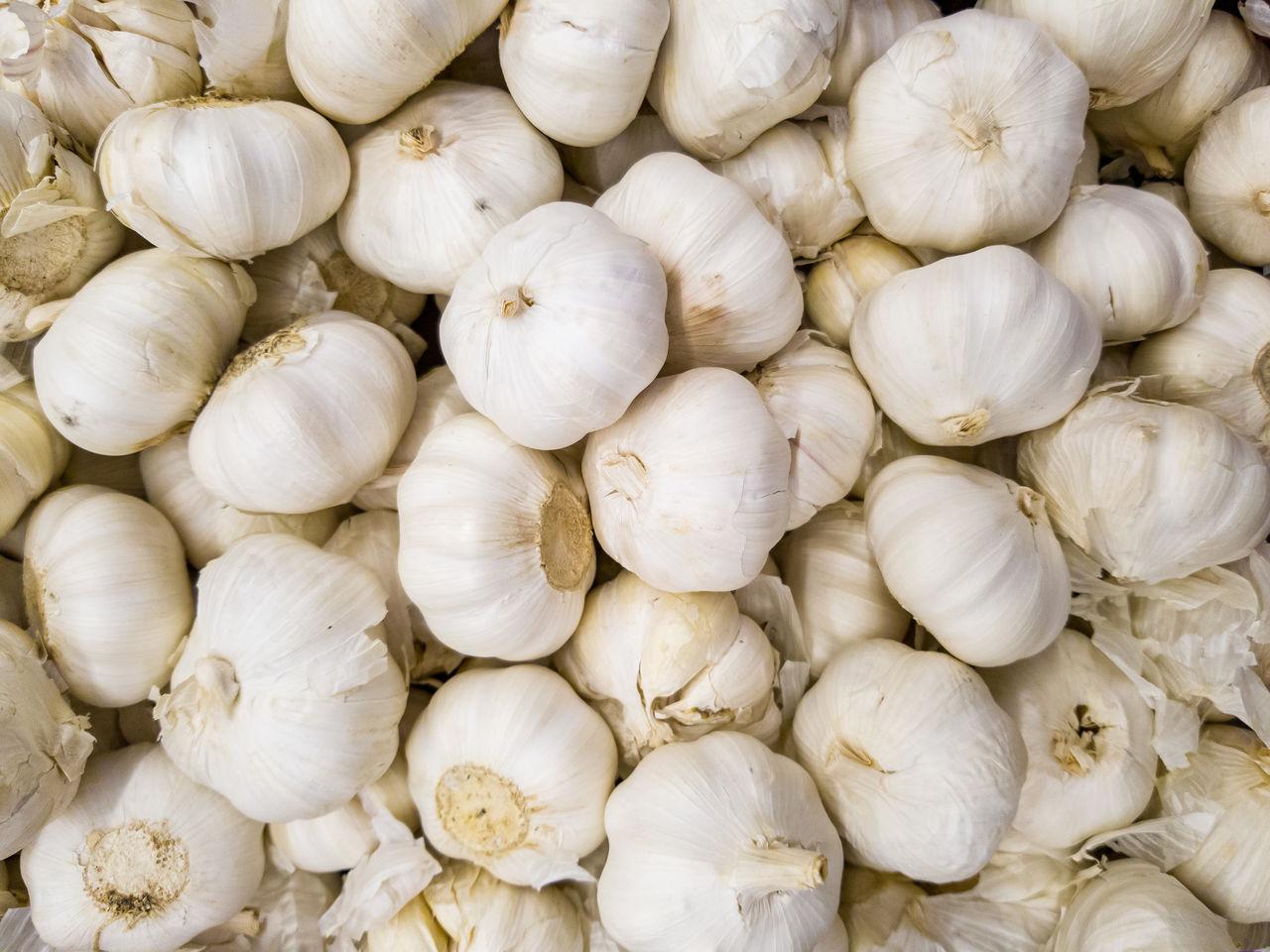 High angle view of pile garlic bulbs, herbs for medicinal purposes.
