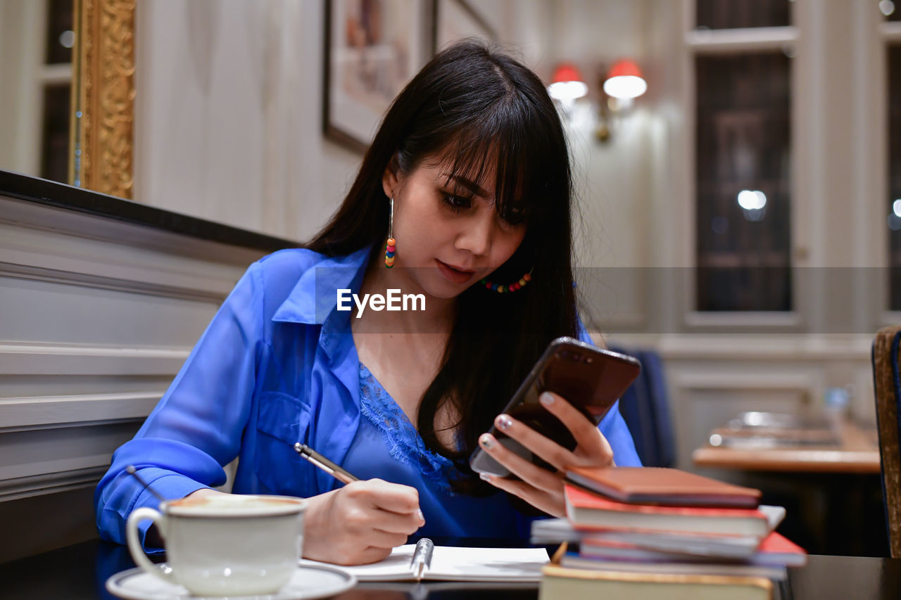 one person, table, real people, food and drink, sitting, front view, drink, mug, holding, young adult, cup, coffee cup, coffee, young women, lifestyles, coffee - drink, indoors, book, publication, focus on foreground, wireless technology, hair, hairstyle