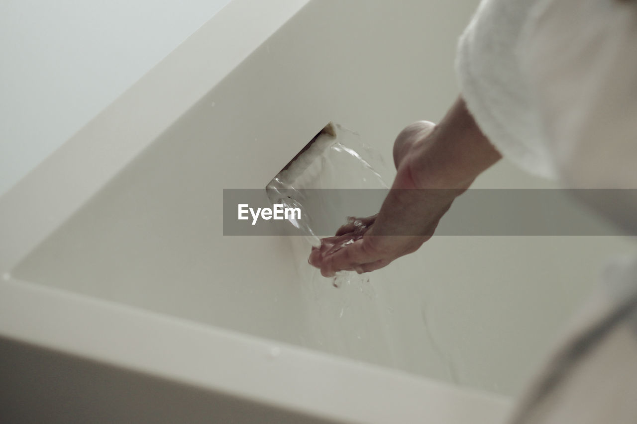 Close-Up Of Hand Touching Water At Bathtub
