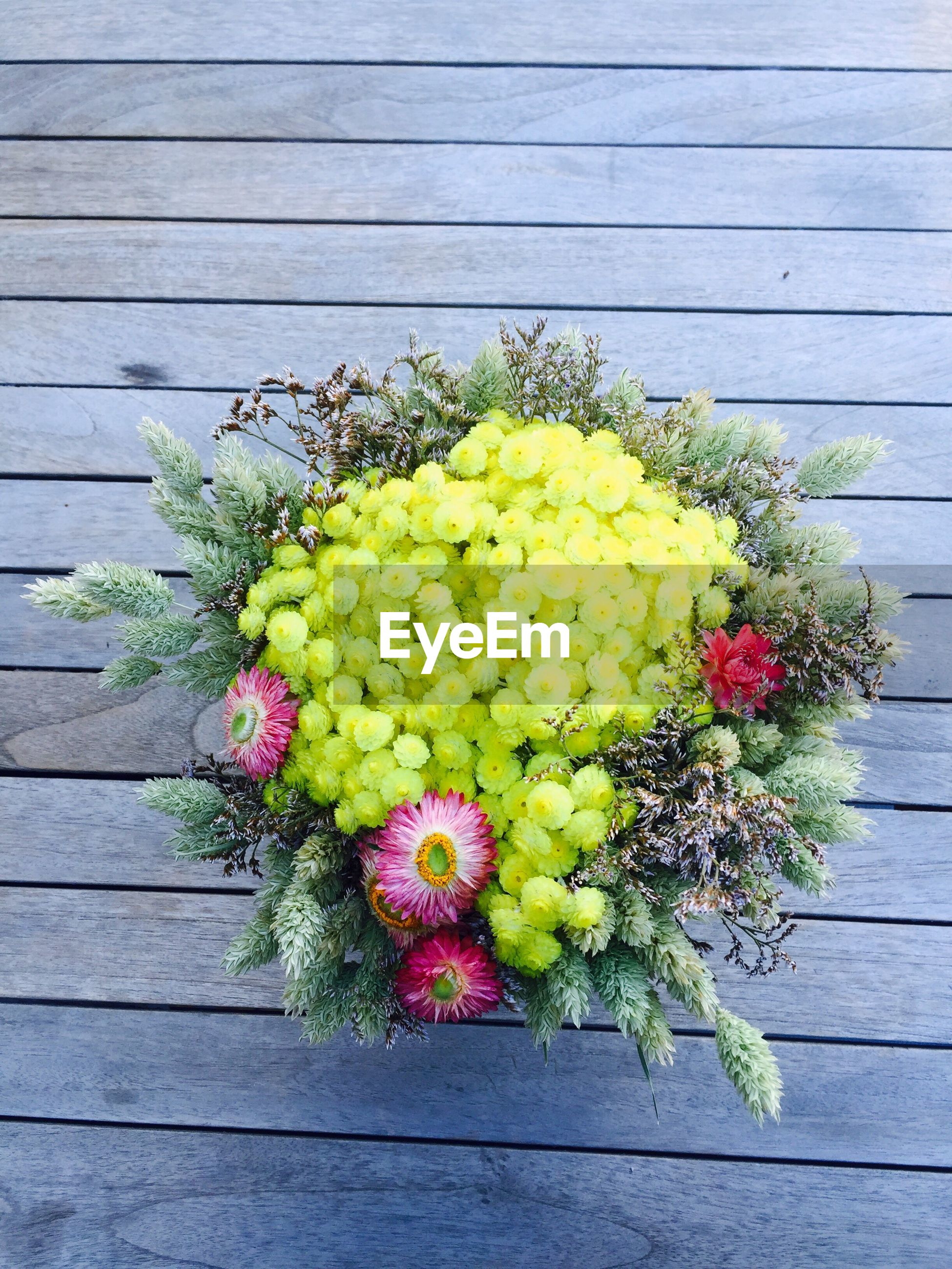 flower, freshness, fragility, wood - material, growth, multi colored, bunch of flowers, high angle view, plant, beauty in nature, wooden, bouquet, flower head, nature, day, yellow, petal, full frame, colorful, vibrant color, abundance, in bloom, red, springtime, wood paneling, outdoors, large group of objects, flower arrangement, arrangement