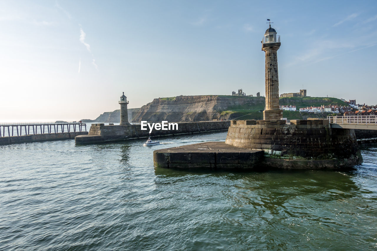 water, built structure, architecture, building exterior, sky, waterfront, tower, sea, nature, travel destinations, building, transportation, no people, travel, tourism, lighthouse, day, city, guidance, outdoors