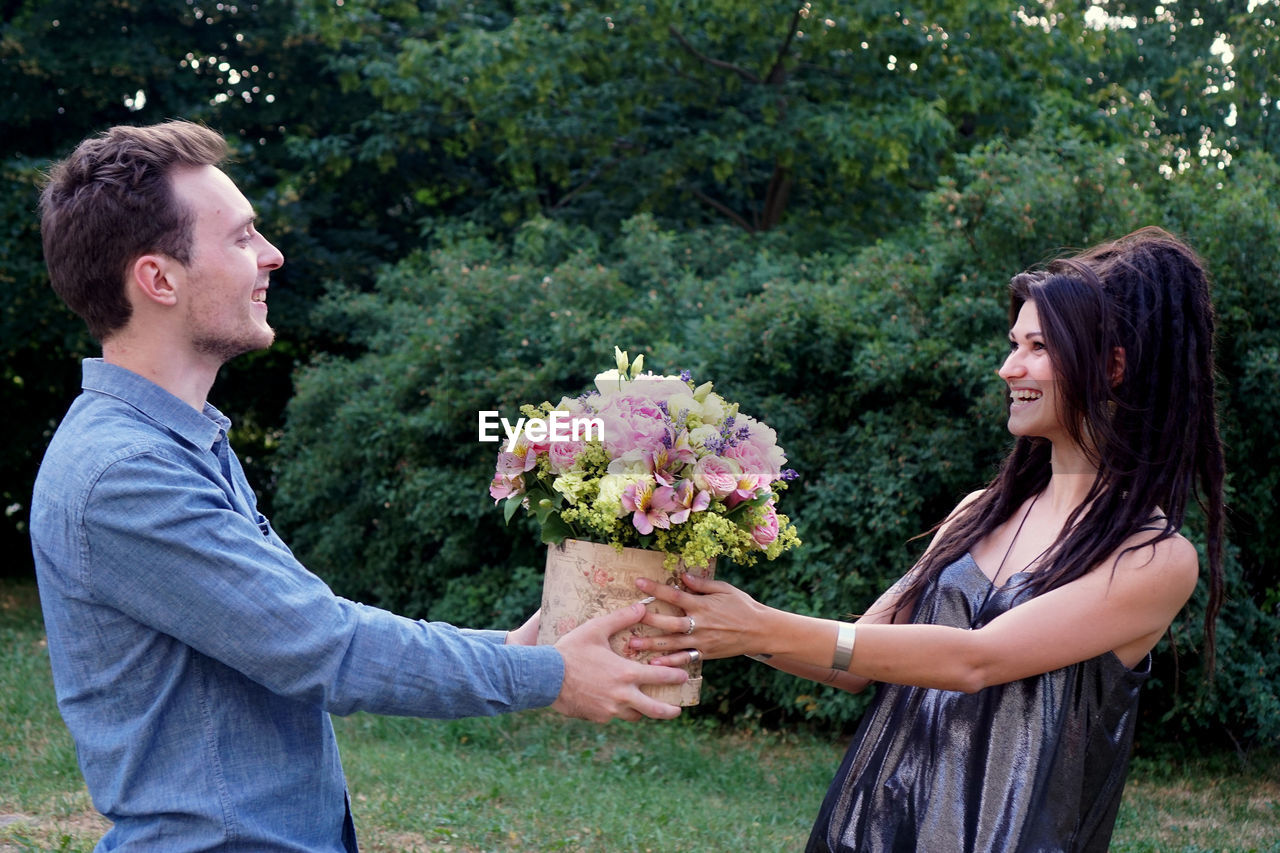 two people, flower, plant, flowering plant, emotion, togetherness, couple - relationship, smiling, men, positive emotion, adult, heterosexual couple, mid adult men, young adult, love, women, side view, mid adult, young women, people, boyfriend, bouquet, outdoors, flower arrangement