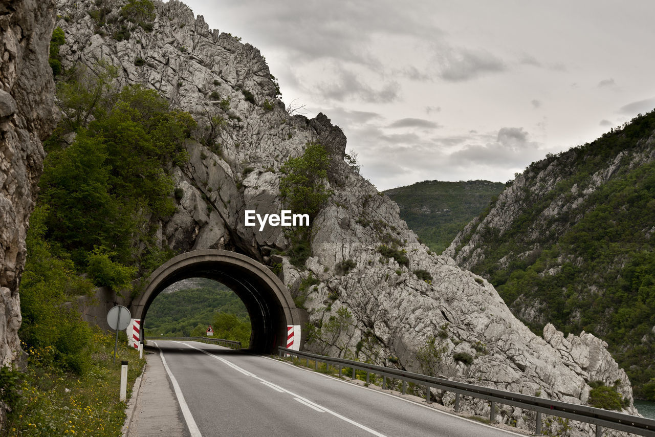 Road passing through cliff against sky