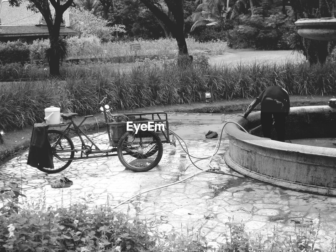 MAN RELAXING ON BICYCLE IN PARK AGAINST TREES