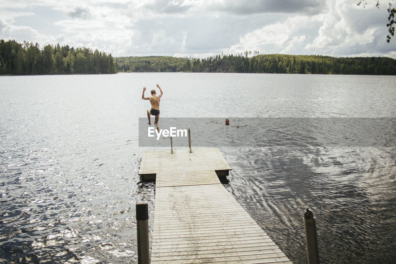 Rear View Of Man Diving Into Lake Against Sky