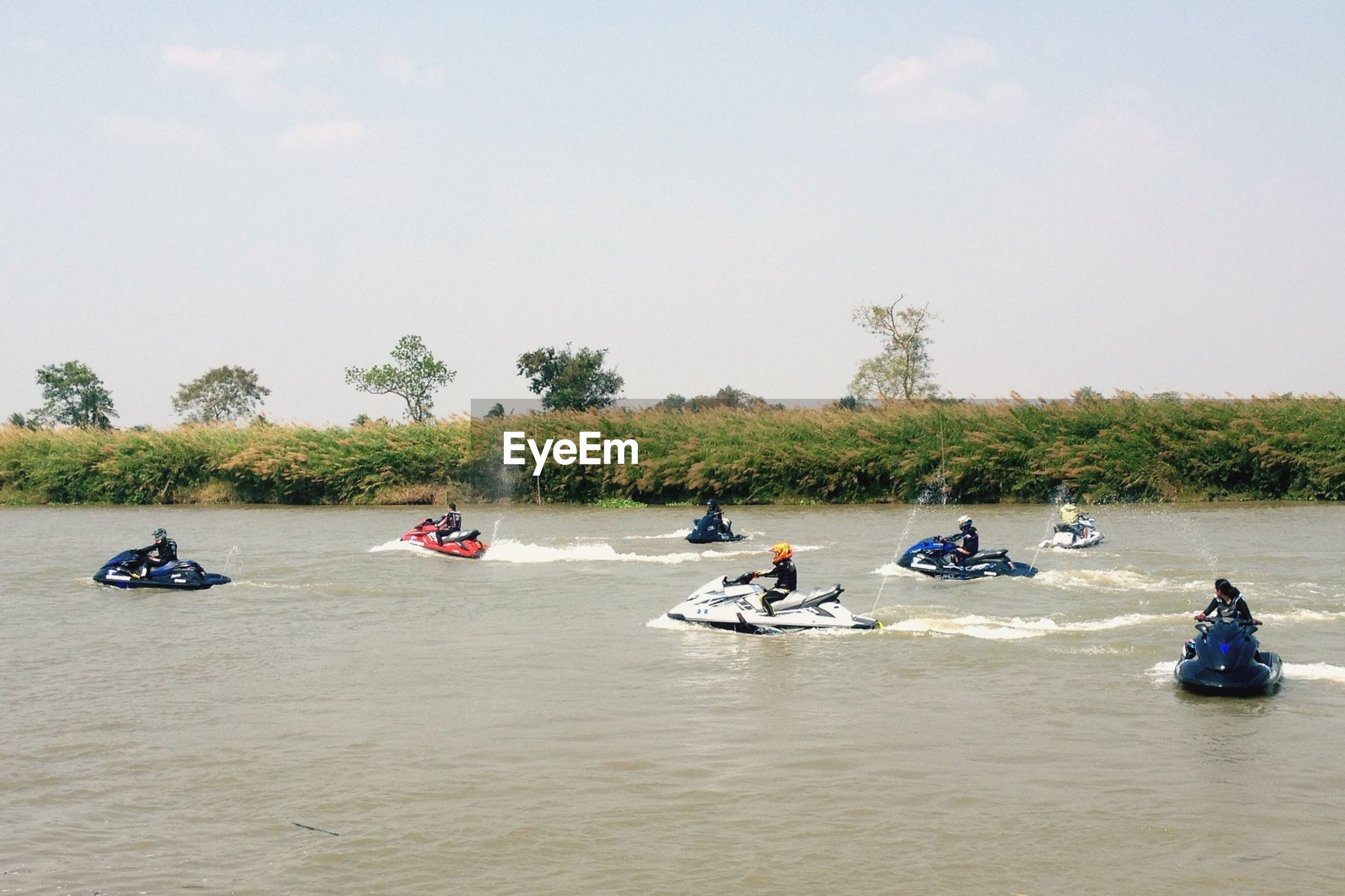 People enjoying on jet boat at river against sky at prachinburi province