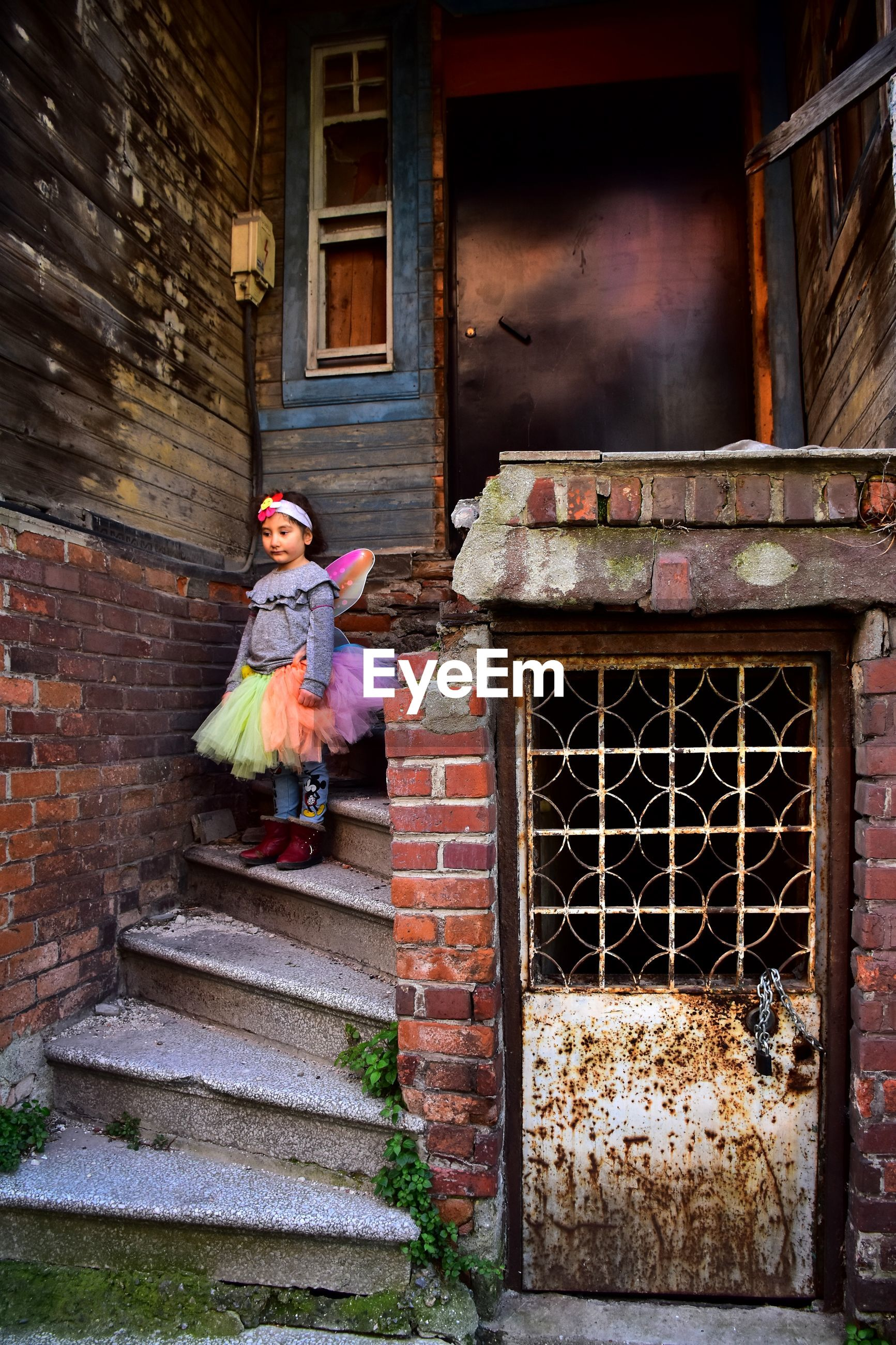 Girl wearing costume while standing on steps outside house