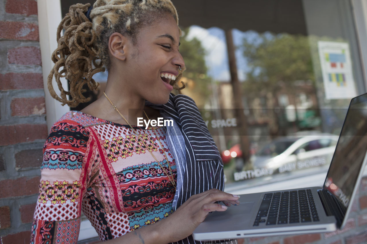 SMILING YOUNG WOMAN USING MOBILE PHONE IN LAPTOP