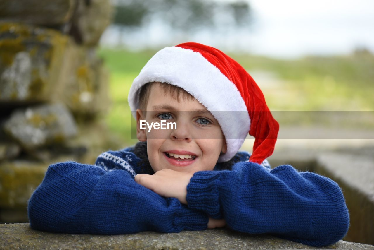 Portrait of boy in santa hat outdoors