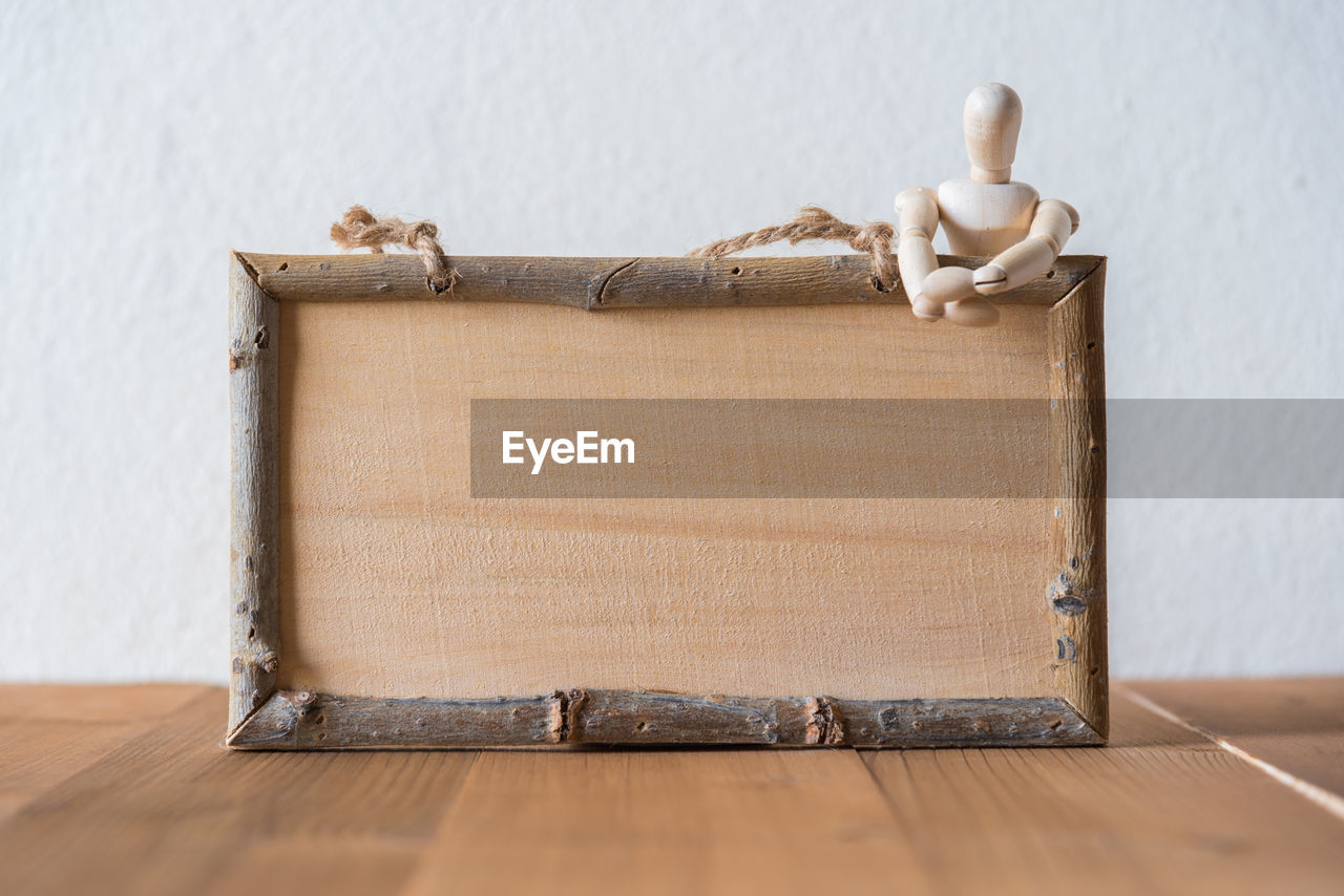 Close-up of wooden figurine with frame on wooden table