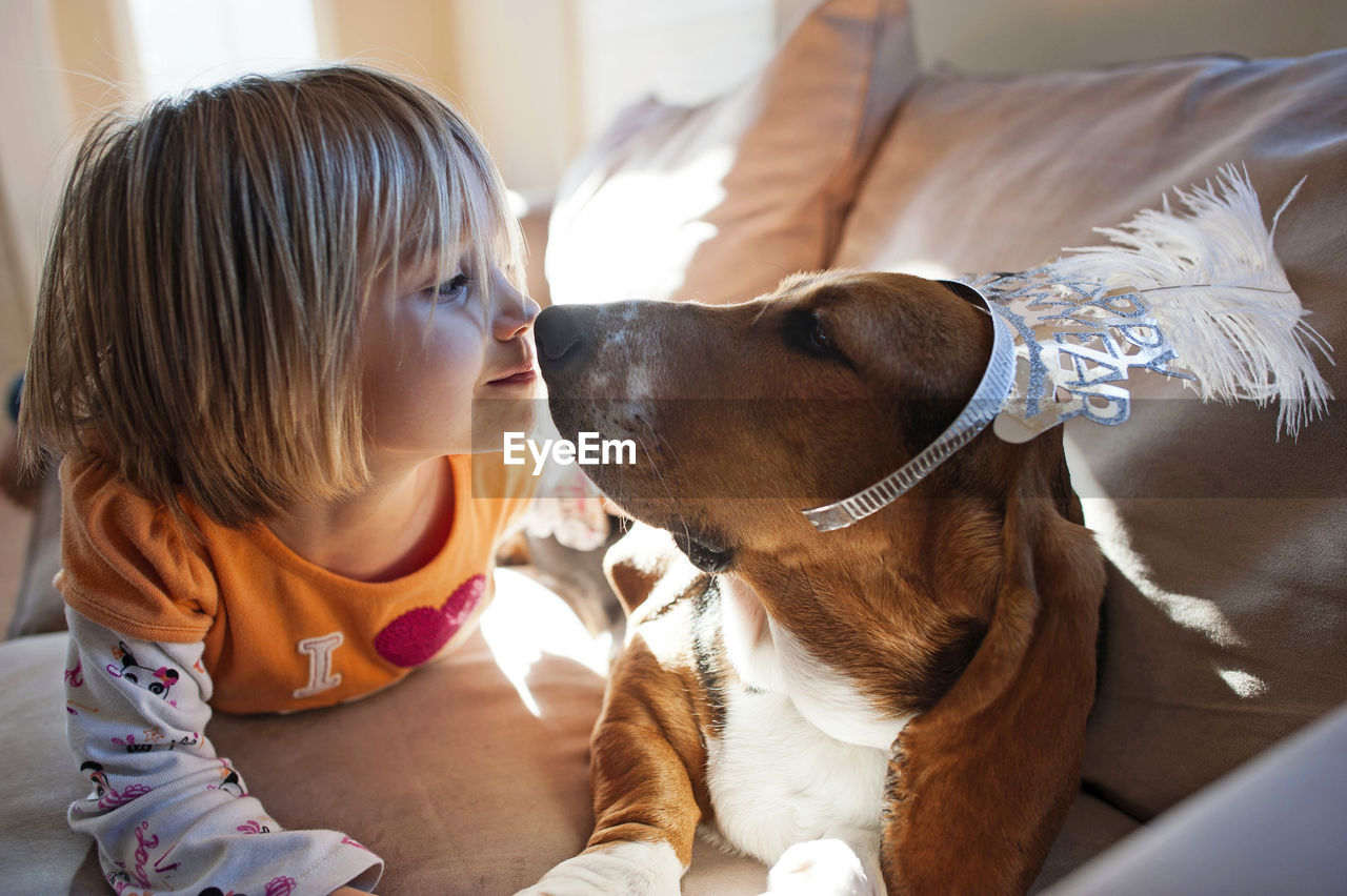 mammal, domestic animals, domestic, one animal, pets, dog, real people, canine, childhood, child, vertebrate, women, girls, indoors, focus on foreground, females, innocence, care, hairstyle, pet owner